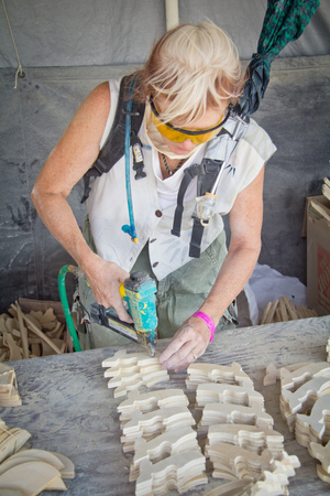 A Temple crewmember makes detailed pieces to apply to the Temple.